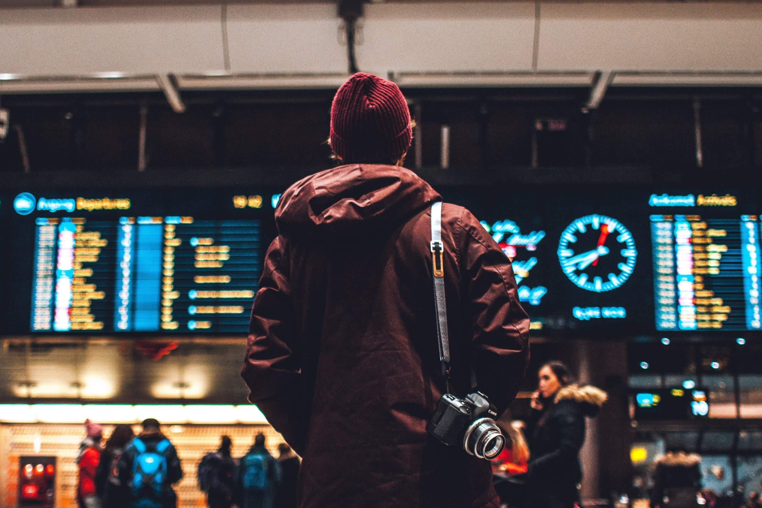 A person next to flights board in an airport