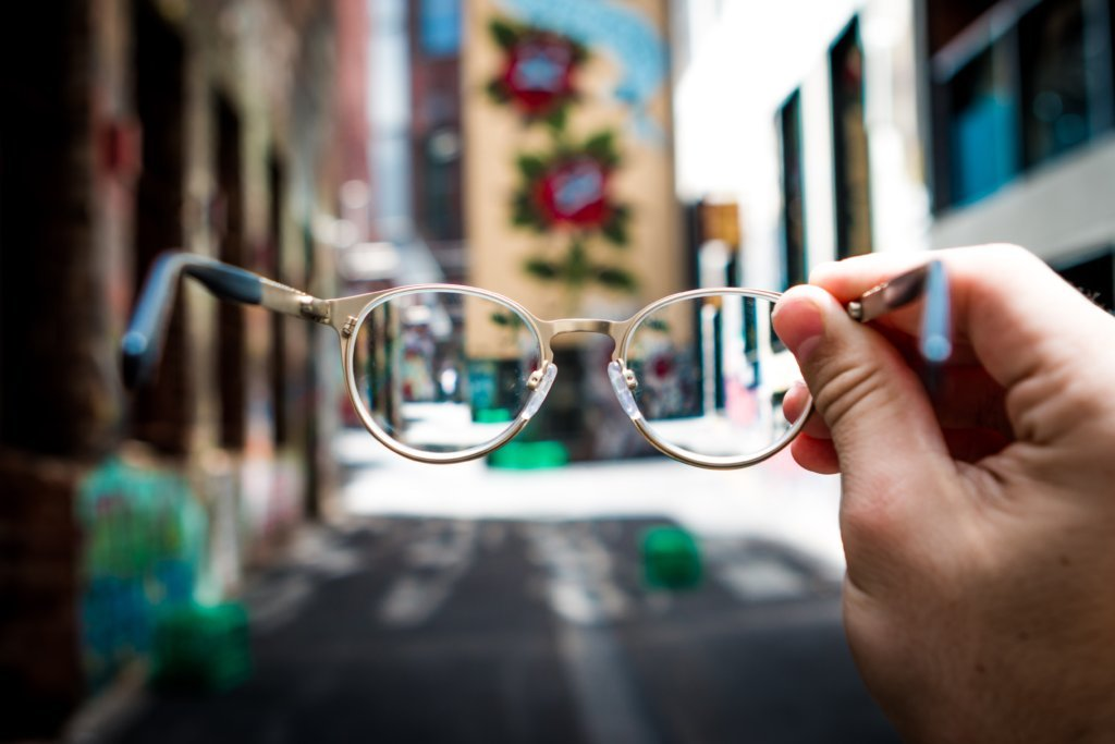 A person holding eyeglasses