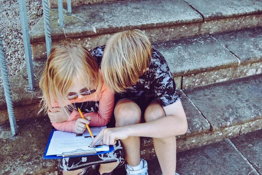 two kids sitting and reading from the same notebook.