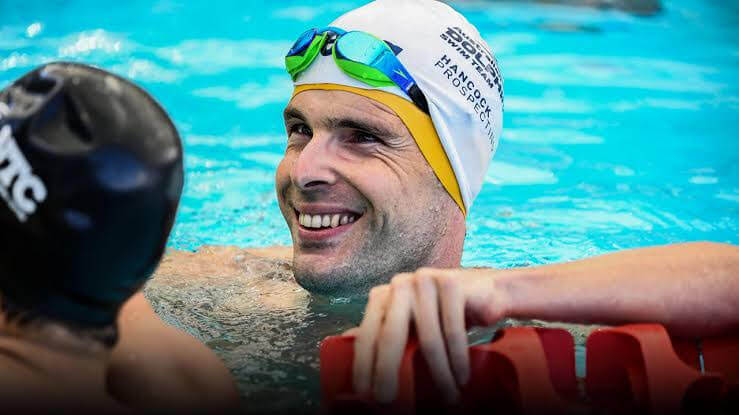Matt is smiling after a race while still inside the swimming pool